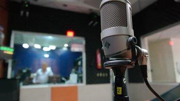 Mikrofon, im Hintergrund ein Aufnahmeraum im Radiostudio